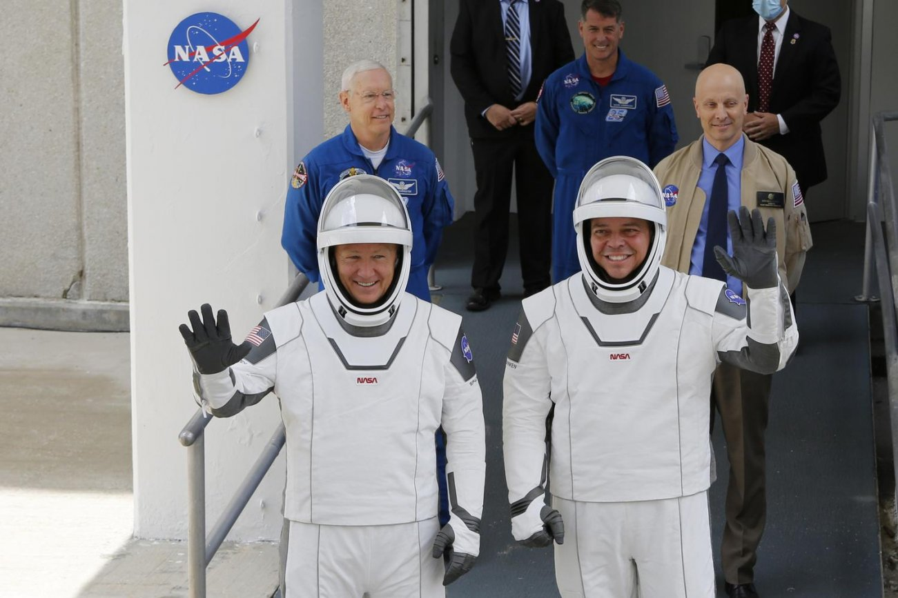 NASA astronauts Douglas Hurley and Robert Behnken wave as they head to Pad39A before the launch of a SpaceX Falcon 9 rocket and Crew Dragon spacecraft at the Kennedy Space Center, in Cape Canaveral, Florida, U.S., May 27, 2020. REUTERS/Joe Skipper