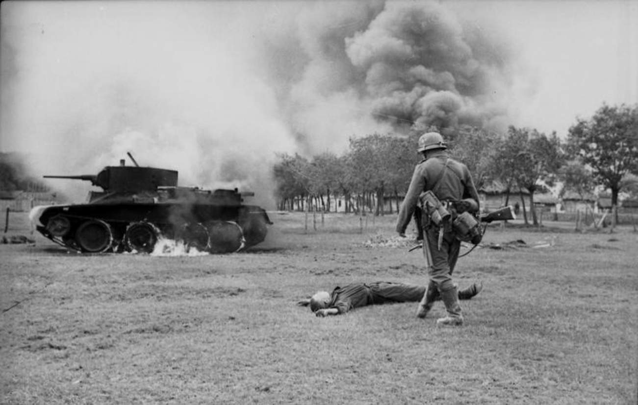 German infantryman in front of fallen Russian tank soldier and burning BT-7 light tank in the southern Soviet Union during the early days of Operation Barbarossa